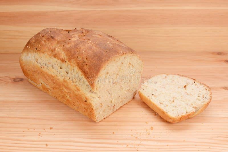 Schneiden Sie Scheibe von einem frisch gebackenen Brotlaib stockbilder