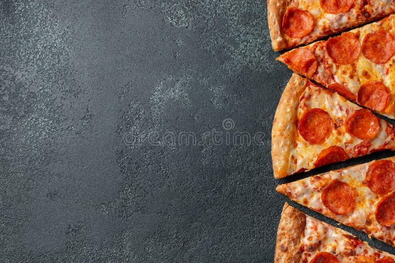 Schneiden Sie in Scheiben köstliche frische Pizza mit Wurstpepperonis und -käse auf einem dunklen Hintergrund Draufsicht mit Kopi stockfotos