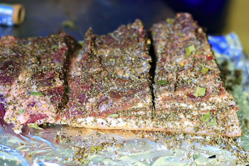 _schneiden Stück von Speck mit ein Schicht von Fleisch sein auf dem Tisch und besprühen mit Gewürz, Pfeffer und Salz Kochen eines stockbild