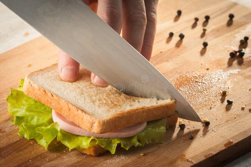 Schneiden von Sandwich mit Brot, Käse, Salat und Schinken mit Händen auf Holzschnitzerei mit Messer stockfoto