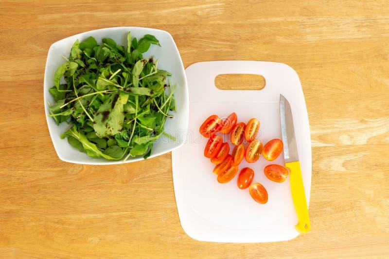 Schneiden von Tomaten auf weißem hackendem Brett mit Messer- und Raketensalat stockbilder