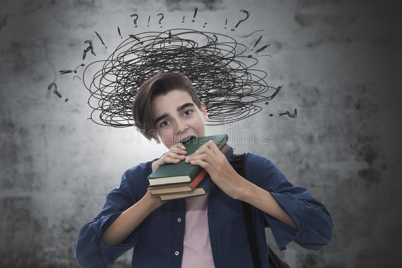 Schneidende Bücher des stressigen Studenten lizenzfreie stockfotografie