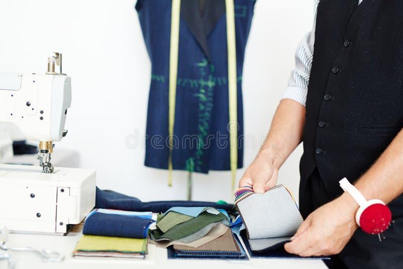 Schneider Choosing Fabric im Atelier stockbilder