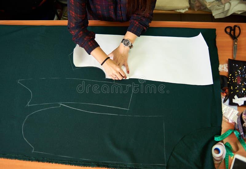 Schneider Worktable im Studio Weibliche Hände, die Kreidemarkierungen von den Papiermustern auf grünem Gewebe machen lizenzfreies stockfoto