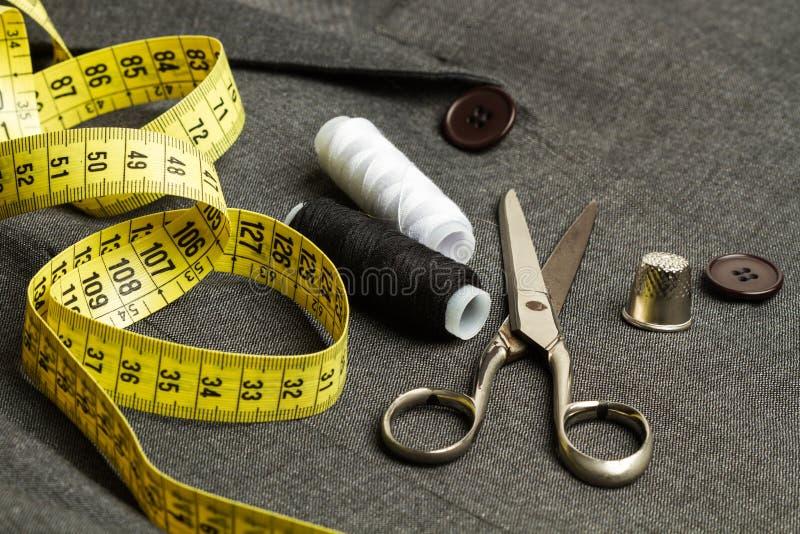 Schneiderwerkzeuge auf einem grauen Anzug stockfotografie