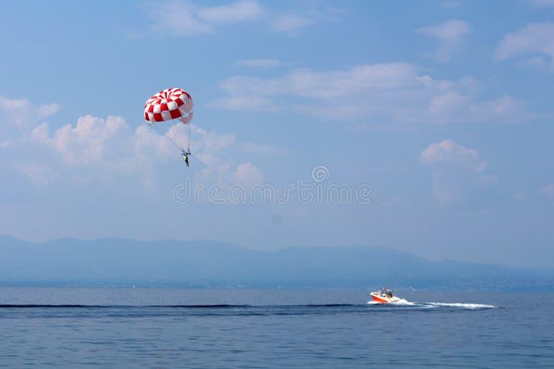 Schnellboot, das Fallschirm mit Touristen auf Panoramablick der lokalen Bucht über ruhigem See mit Bergen und bewölktem blauem Hi stockbild