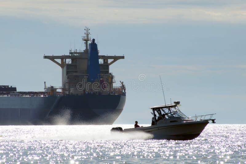 Schnellboot, das in volle Geschwindigkeit vor einem Transozean conta überschreitet lizenzfreie stockfotos