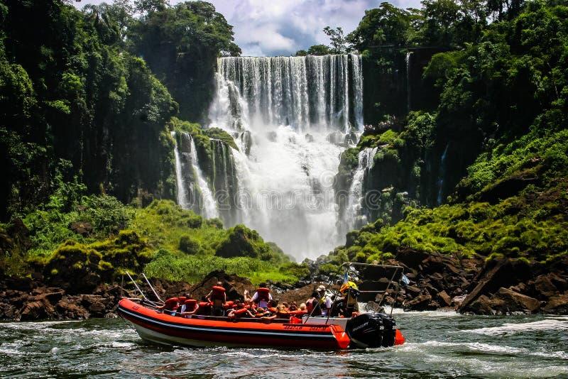 Schnellbootfahrten unter dem Wasser, das in den Iguacu-Fällen in Iguacu, Brasilien kaskadiert stockfoto