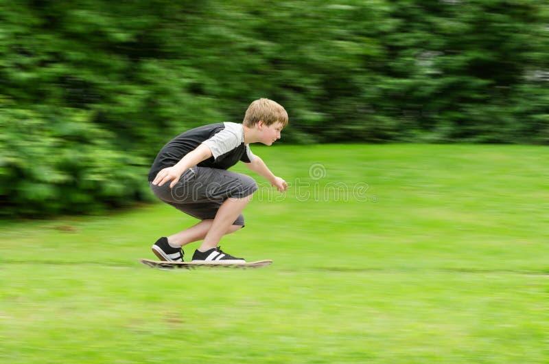 Schnelle Fahrten des Kerls des jungen jugendlich ein Skateboard im Park stockbild