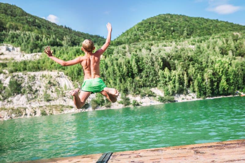 Schneller laufender Junge, der in Gebirgssee vom Dock springt Unvorsichtiges Kindheitskonzeptbild lizenzfreies stockbild