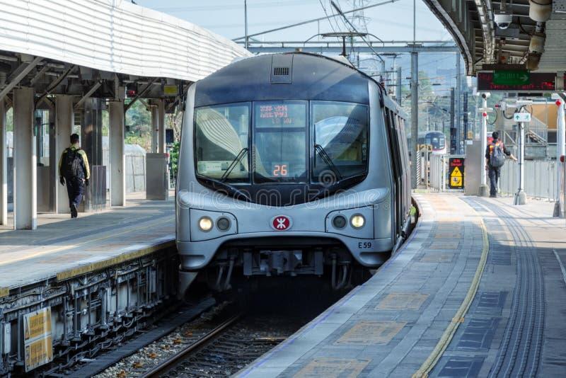 Schneller Metrozug kommt zu Freiluftstation, Leute gehen auf Plattform MTR Corporation stockfotografie