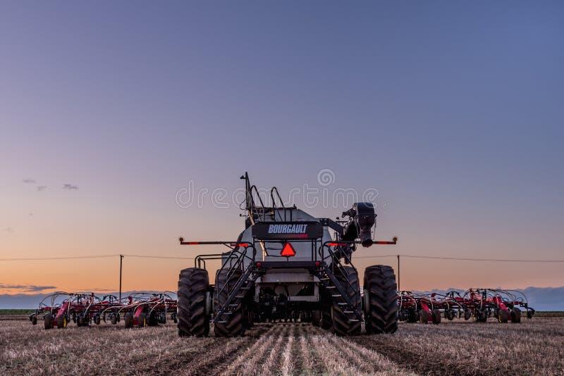 Schneller Strom, SK/Canada- 10. Mai 2019: Traktor- und Bourgault-Druckluftbohrer, der Ausr?stung auf dem Gebiet s?t stockbild