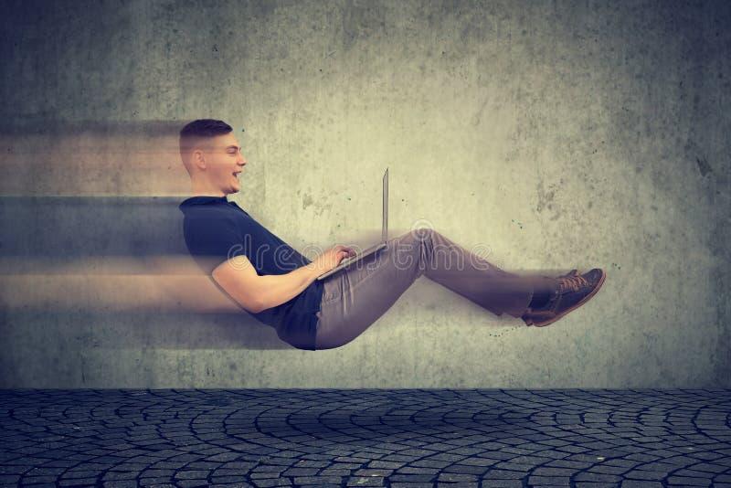 Schnelles Internet-Konzept Frei schwebender junger Geschäftsmann auf Straße unter Verwendung des Laptops lizenzfreie stockbilder
