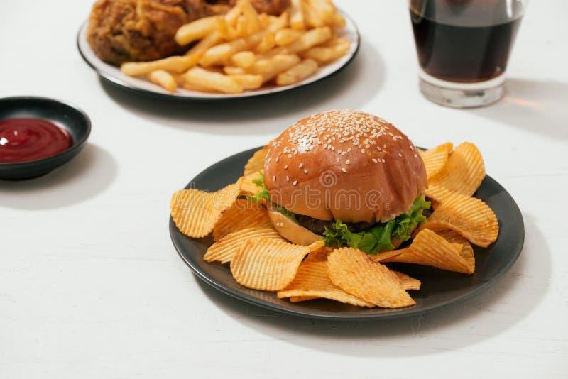 Schnellimbisshamburger mit Satz gebratenem knusperigem Huhn und Pommes-Frites, Eiskolabaum auf der Seite lizenzfreies stockbild