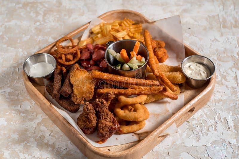 Schnellimbissprodukte: Zwiebelringe, Pommes-Frites und gebratenes Huhn auf dunkler Tabelle, Draufsicht stockbild