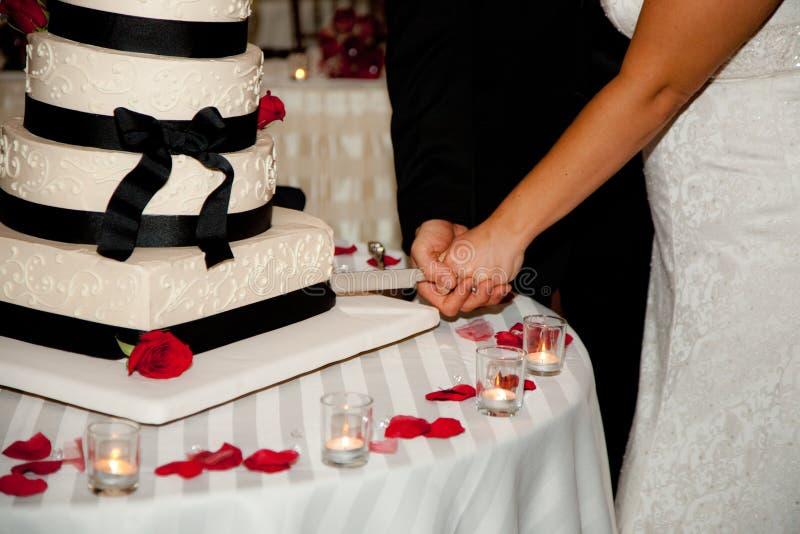 Schnitt eines Hochzeits-Kuchens lizenzfreies stockfoto