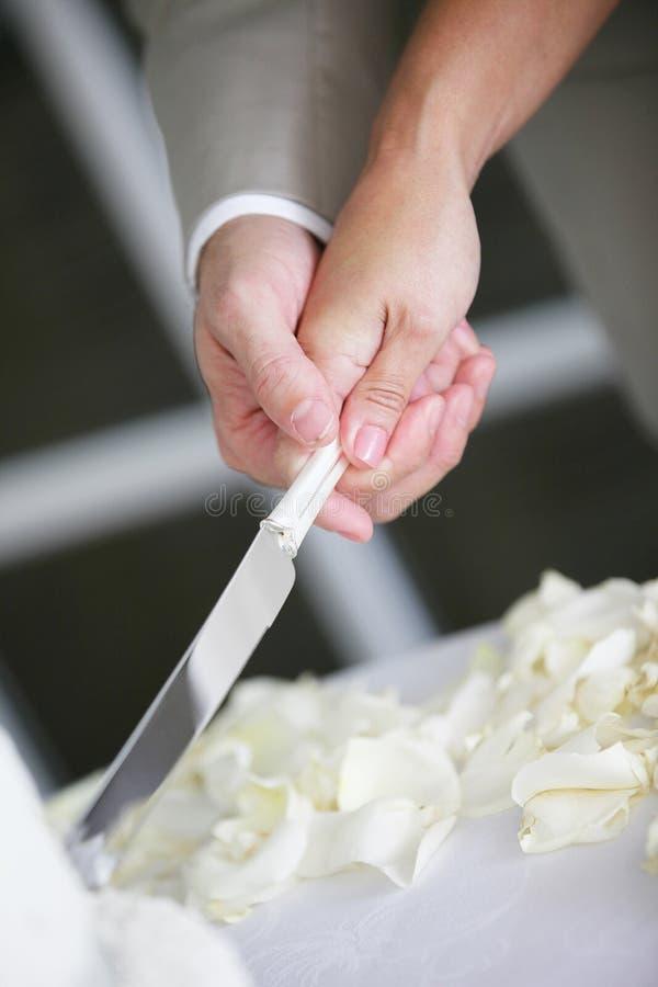 Schnitt eines Hochzeits-Kuchens stockfotos