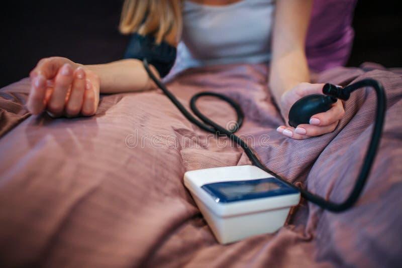Schnittansicht der jungen Frau sitzend auf Bett und mesuring blod Druck mit Spezialwerkzeug Sie squizes Pumpe Frau ist stockfoto