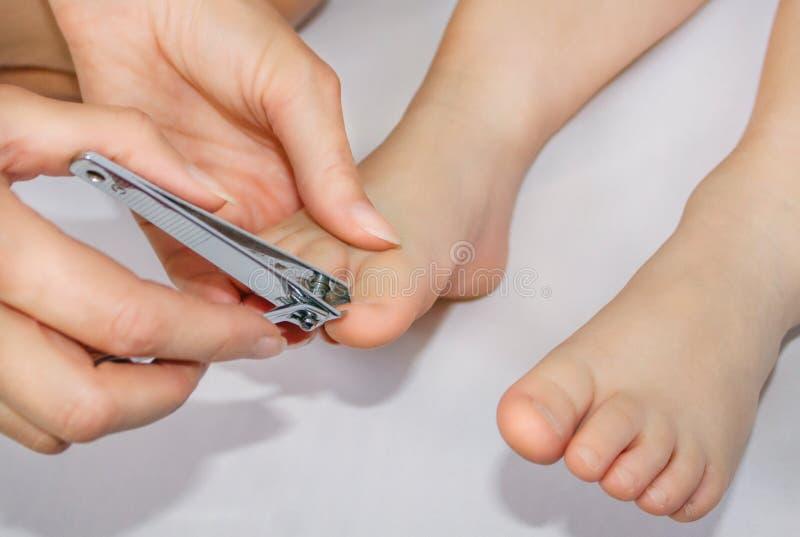 Schnittnägel auf den Füßen eines Kindes Interessieren für das Baby lizenzfreie stockfotos
