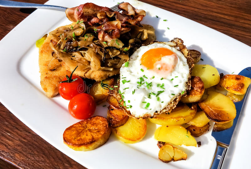 Schnitzel with fried egg, bacon and fried potatoes royalty free stock images