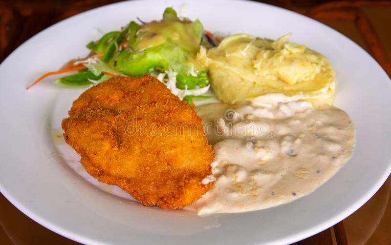 Schnitzel with mashed potato on white plate. Fried chicken cutlet top view photo on wooden table. Tasty lunch served royalty free stock image