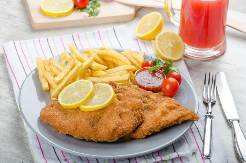 Schnitzel med fransmansmåfiskar och ett kryddigt dopp arkivfoto