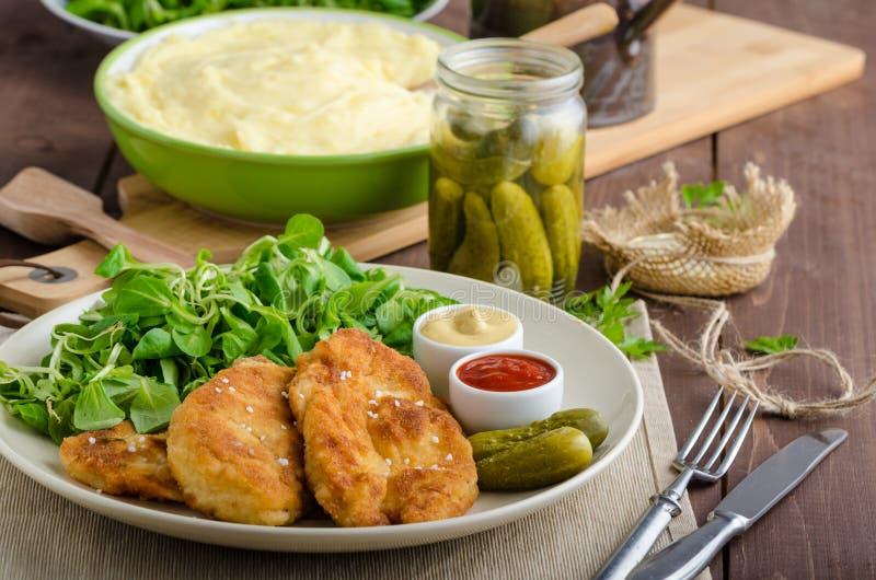 Schnitzel met fijngestampte aardappels en salade stock foto