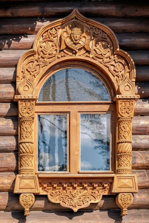 Schnitzen des verzierten Fensters auf gezimmerter Hausmauer stockfotos