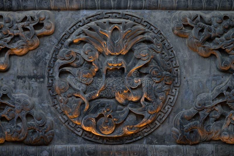 Schnitzen eines chinesischen Drachen in einem Achteck auf einer Tempelwand in Xi'an, Shaanxi, China stockbilder