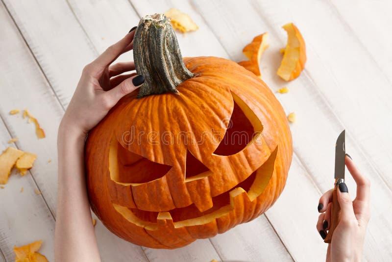 Schnitzen von Halloween-Kürbis in Steckfassung-Olaterne, Abschluss herauf Ansicht lizenzfreie stockfotos
