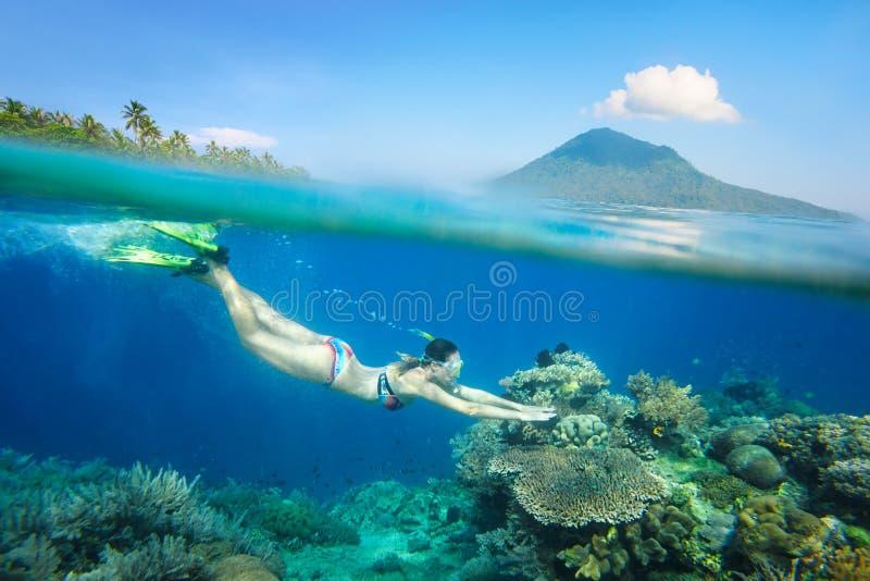 Schnorcheln der Frau über dem schönen Korallenriff stockfoto