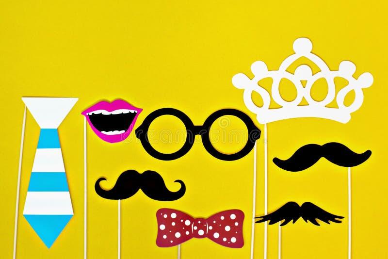 Schnurrbart, Bindung, Gläser, roter Mund auf hölzernen Stöcken gegen Spenden eines helle gelbe Hintergrund Monats stockbild