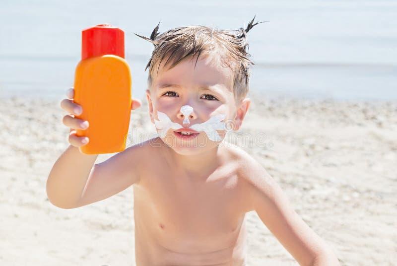 Schnurrbartkatzen-Zeichnungslichtschutz u. x28; Sonnenbräune lotion& x29; auf Hippie-Jungengesicht bevor dem Bräunen während der  stockfotos