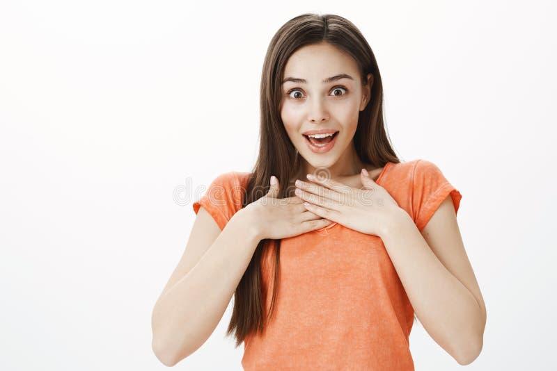 Schockierende Freundin, die enormen Eimer Rosen empfängt Innenschuß der überraschten und berührten entzückenden Frau im orange T- stockfotos