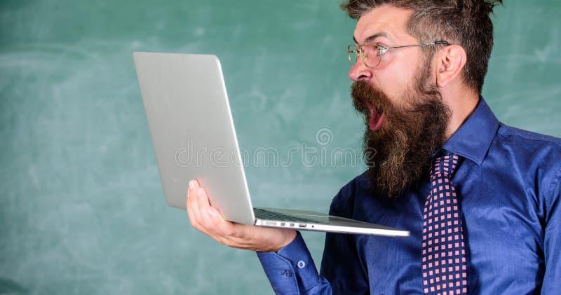 Schockierende Informationen Hippie-Lehrerabnutzungsbrillen und -krawatte hält surfendes Internet des Laptops Schockierende Nachri lizenzfreies stockbild
