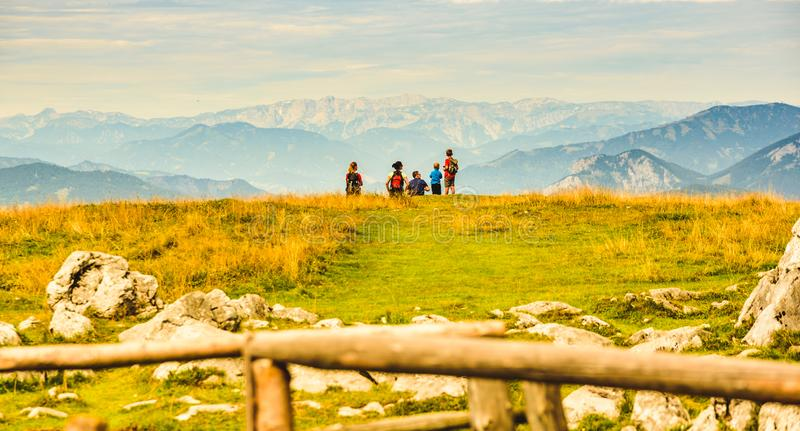Family sitting on grass and enjoying view over mountains from Schockl in Graz, Austria. Schockl, Styria, Austria - 17.08.2019 : View from a peak of rocky stock photo