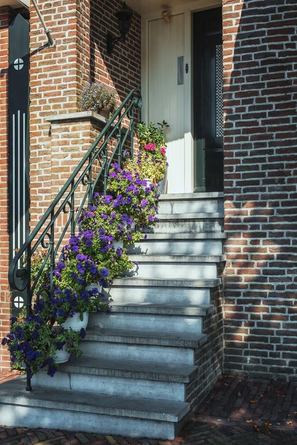 Schodki dekorowali z petuniami dzwi wejściowy dom w t obraz royalty free