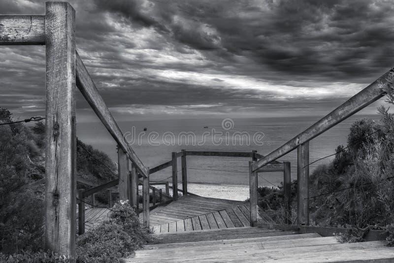 Schodki plaża, ocean i chmurny niebo, obrazy stock
