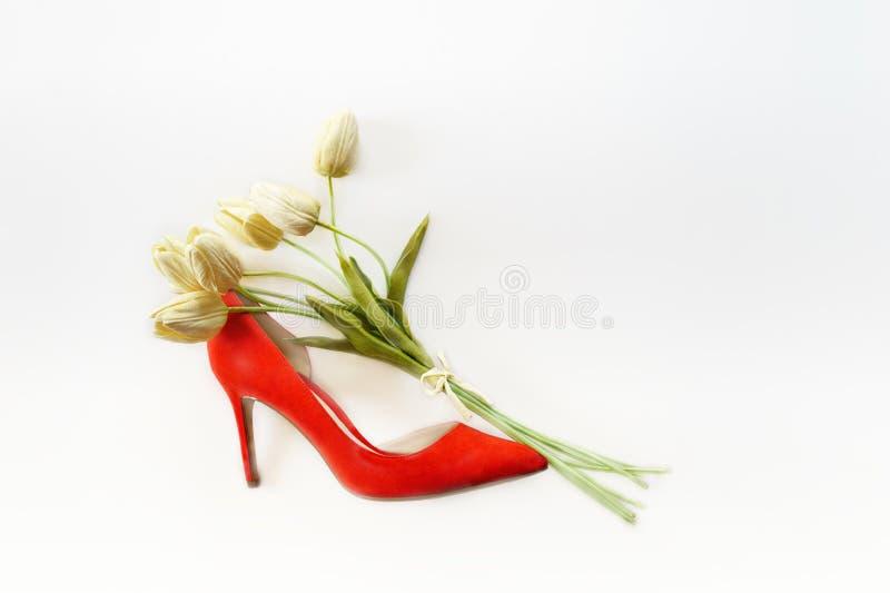 Schoen van de dames de rode hoge die hiel met van het boeket witte tulpen en exemplaar ruimte op witte achtergrond wordt gevuld V royalty-vrije stock fotografie