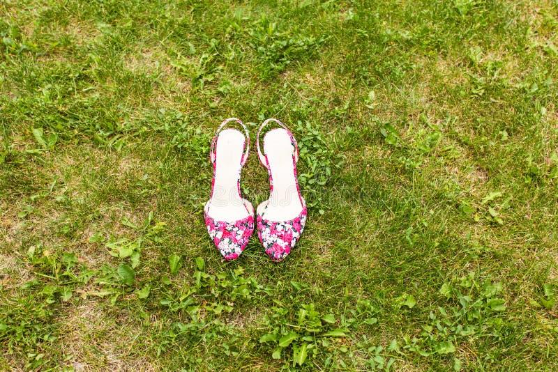 Schoenen van een vrouw op groen gras Het concept van de de zomervakantie, daglicht royalty-vrije stock afbeeldingen