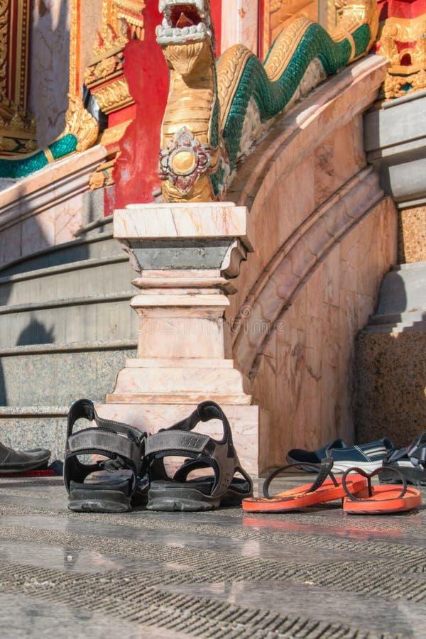 Schoenen verlaten bij de ingang aan de Boeddhistische tempel Concept het waarnemen van tradities, tolerantie Naleving van de rege royalty-vrije stock afbeeldingen