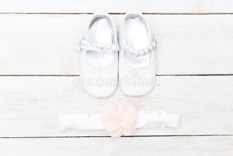 Schoenen voor babys en een verband voor haar op een witte houten backgr stock afbeelding