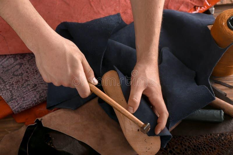 Schoenmaker die met schoenspanner en hamer bij fabriek werken royalty-vrije stock afbeeldingen
