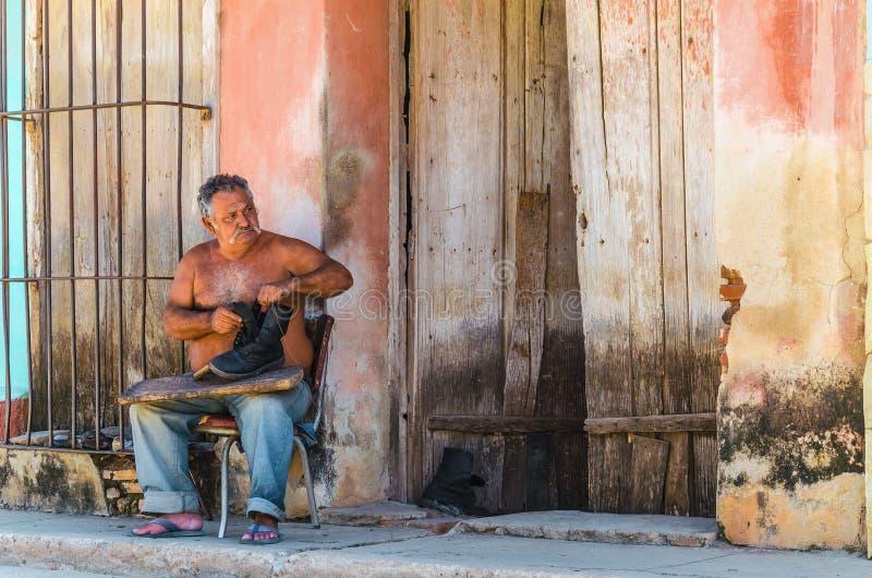 Schoenmaker die schoenen op een straat in Trinidad, Cuba herstellen stock foto's
