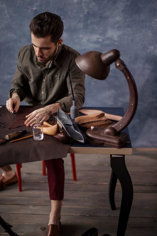 Schoenmaker die stof voor het maken van in schoenen voorbereiden stock afbeelding