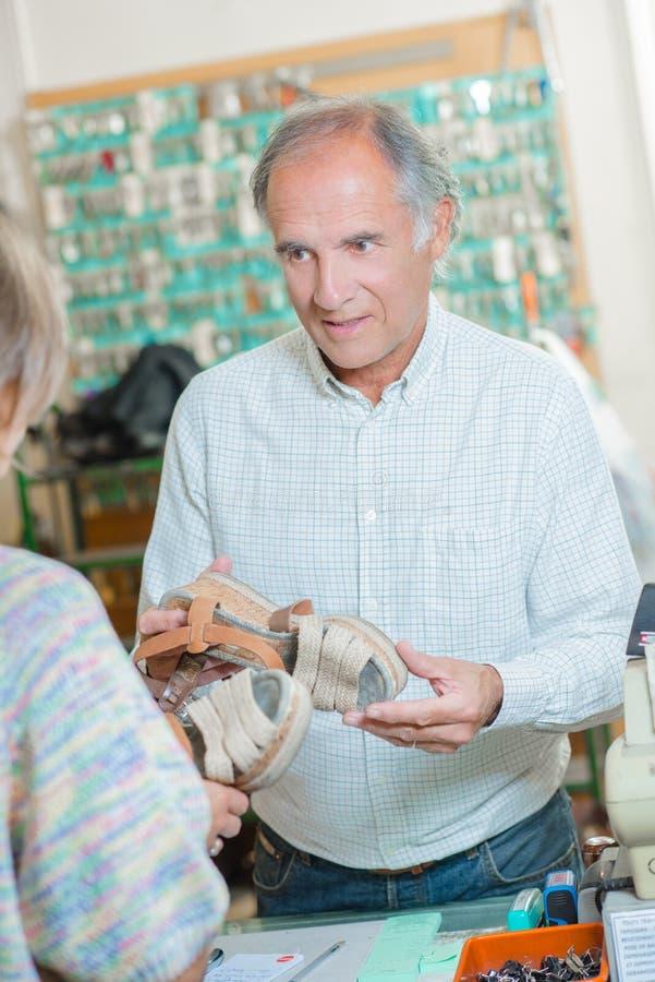 Schoenmaker die wat verklaren aan schoen moet worden gedaan royalty-vrije stock fotografie