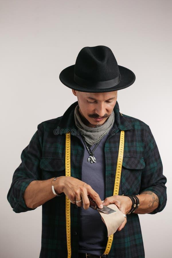 Schoenmaker in modieuze hoed en maatregelenband die die naald inpassen in studio wordt geïsoleerd royalty-vrije stock foto's