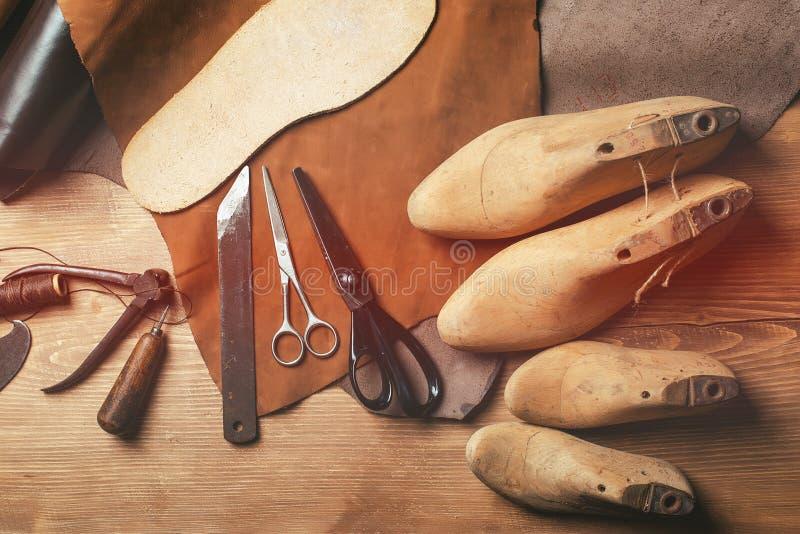 Schoenmakershulpmiddelen in workshop over de houten lijst Hoogste mening stock fotografie
