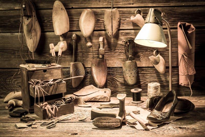 Schoenmakersworkshop met hulpmiddelen, schoenen en kant stock afbeelding