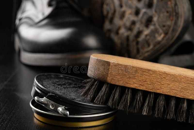 Schoenpoetsmiddel, borstel en zwarte militaire laarzen Oppoetsende en schoonmakende schoenen op een zwarte lijst royalty-vrije stock foto